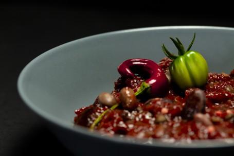 Kichererbsen-Chili - In einem dunklen runden Suppenteller befindet sich das dunkelrote Kichererbsen-Chili. Die Kichererbsen sind gut sichtbar. garniert ist das ganze mit einer dunkelroten Chilischote und einer kleinen grünen Tomate. (Foto: Tobias Schneider-Lenz - Nicht zur freien Verwendung)