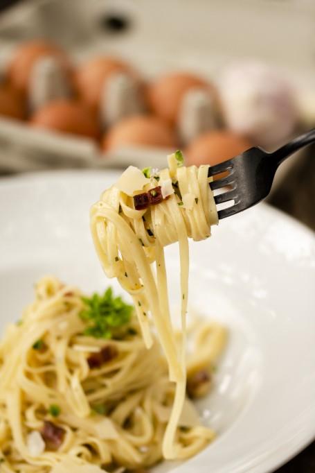 Spaghetti Carbonara - Spaghettinudeln aufgewickelt auf einer Gabel, Käseraspeln und Speckwürfel sind zu erkennen. Im Hintergrund befindet sich ein weißes Teller mit einer Portion Spaghetti Carbonara. (Foto: Tobias Schneider-Lenz - Nicht zur freien Verwendung)