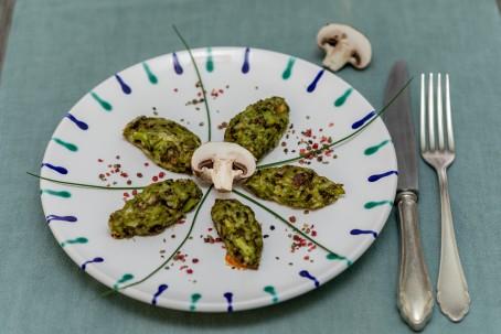 Brokkoli - Pilz - Käse - Nuggets - Auf einer blaugrauen Unterlage steht ein weißer Teller mit blauer und grüner Verzierung am Rand. Darauf liegen 5 grüne Nockerl in der größe von Griesnockerl im Kreis angeordnet. Die Mitte bildet ein halbes Champignon. Die Nocker sind durch Schnittlauchhalme getrennt die unter dem Champignon in der Mitte zusammentreffen. Etwas Farbe bringen bunte grob zerhackte Pfefferkörner auf den Teller. Im Hintergrund des Tellers befindet sich die zweite Hälfte des Chamoignon und rechts neben dem Teller liegen Messer und Gabel bereit. (Foto: VrK/Achim Mandler Photography - Nicht zur freien Verwendung)