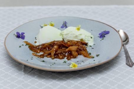 Karamellisierte Pilze - Auf einem grauen Tischtuck mit weißem Muster steht ein blaugrau mellierter Teller. Auf dem Teller sind braun karamellisierte fein geschnittene Pilze zu erkennen. Dahinter sind 2 Kugeln Vanilleeis zu sehen. Rundherum liegen am Tellerrand blaue und gelbe Blüten als Dekoration. Neben dem Teller liegt ein Suppenlöffel. (Foto: VrK/Achim Mandler Photography - Nicht zur freien Verwendung)