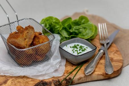 Austernpilze mit Joghurt-Dipp - Auf einem Holzbrett steht auf der linken Seite ein kleines eckiges Sieb in dem sich einige panierte Austernpilze befinden. Das Sieb steht auf einem weißen Papier. Neben dem Sieb steht ein kleines eckiges Schüsserl mit dem weißen Joghurt-Dipp, der mit grob geschnittenem Schnittlauch garniert ist. Hinter dem Schüsserl ist ein Salatblatt dekorativ platziert. Rechts neben dem Schüsserl liegen Messer und Gabel bereit zum Verzehr der leckeren Pilze. (Foto: VrK/Achim Mandler Photography - Nicht zur freien Verwendung)