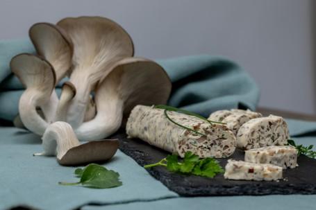 Pilzbutter - Auf einem blauen Tuch sind auf der linken Seite einige Pilze platziert. Auf der rechten Seite befindet sich die zu einer kleinen Rolle geformte Pilzbutter. 5 zentimeterdicke Scheiben der Pilzbutter sind bereits hergeschnitten und dekorativ neben der Rolle platziert. Die kleinen braunen Pilzstückchen sind darin deutlich zu erkennen. Es wurden verschiedene Kräuter wie Petersilie, Thymian und Schnittlauch auf und neben die Pilzbutter gelegt. (Foto: VrK/Achim Mandler Photography - Nicht zur freien Verwendung)