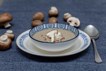 Pilzcremesuppe - Auf  blauem Untergrund steht ein weißer Teller mit blauer Verziehrung. Auf dem Teller befindet sich eine Suppenschüssel ebenfalls mit blauer Verziehrung. In der Suppenschüssel ist die hellbraune Pilzcremesuppe angerichtet. Die Suppe ist in der Mitte mit einem Tupfen Schlagobers einem Stück Champignon und bunten Pfefferkörnern garniert. Auf der linken Seite und hinter dem Teller liegen einige braune Chamoignons verteilt. Rechts neben dem Teller liegt ein silbener Suppenlöffel. (Foto: VrK/Achim Mandler Photography - Nicht zur freien Verwendung)