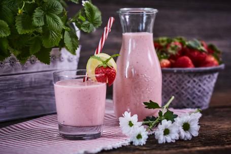 Erdbeer Joghurt Drink - Der Erdbeer Joghurt Drink wird in einem kleinen Gläschen auf einem weiß-roten Tischtuch serviert. Er ist durch einen Strohhalm leicht zu trinken. Das Glas ist mit einer Erdbeere und mit einer Zitrone verziert.  Im Hintergrund befinden sich ein gefüllter Krug und Körbe mit Früchten und Erdbeerpflanzen. (Foto: VrK/Franz Gleiß - Nicht zur freien Verwendung)