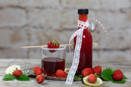 Erdbeersirup - Auf grauem Hintergrund auf einem Metalltablett steht eine Flasche, mit rotem Inhalt, garniert mit einer weißen Masche, danebenein Glas halbvoll, garniert mit einer Erdbeere auf einem Spieß, der Rand des Glases gezuckert, daneben liegen Erdbeeren und grüne Deko bzw. Zitronenscheiben (Foto: VrK/Achim Mandler Photography - Nicht zur freien Verwendung)