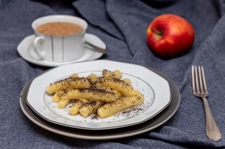 Schupfnudeln mit Mohn - Auf einem weißen Teller liegen gelbfarbene, fingerdicke Nudeln garniert mit geriebenen Mohn, daneben eine Tasse Kaffe und ein Apfel (Foto: VrK/Achim Mandler Photography - Nicht zur freien Verwendung)