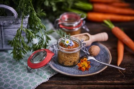 Karottenkuchen im Glas - Auf einem blau melierten Teller befindet sich im Glas der Karottenkuchen.  Nüsse, Karotten und Kräuter dienen einer wunderschönen Verzierung. (Foto: VrK/Franz Gleiß - Nicht zur freien Verwendung)