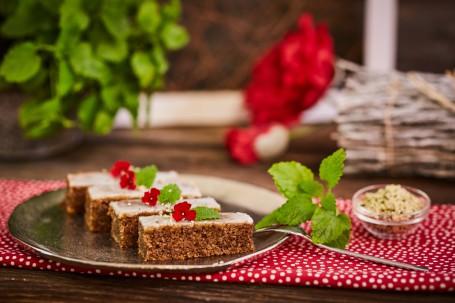Hanfnüsschen Schnitte - Auf einem roten Tischtuch mit weißen Punkten ist ein silberner Teller. Darauf sind vier Hanfnüsschen Schnitten zu sehen. Diese sind mit roten Blüten und grünen Kräutern verziert. Eine Gabel zum Essen und eine Glasschüssel mit Beilage sind bereitgestellt. (Foto: VrK/Franz Gleiß - Nicht zur freien Verwendung)
