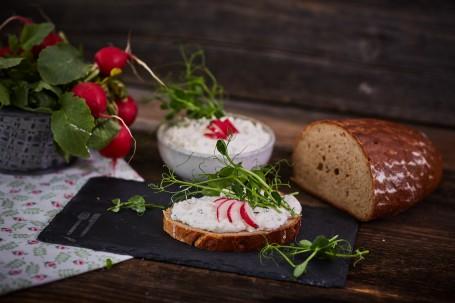 Radieschen-Kräuter Aufstich - Auf einem schwarzen Untersetzer ist ein Brot mit Radieschen-Kräuter-Aufstrich hergerichtet. Das Brot ist mit vier kleinen Radieschen-Scheiben und Kräutern verziert. Auf dem schwarzen Untersetzer befindet sich links ein Symbol für Messer und Gabel. Auf der linken Seite ist ein Tischtuch mit grün-roten Blumen. Darauf befindet sich ein Korb mit Radieschen-Pflanzen. Hinter dem Brot ist eine Schüssel mit Aufstrich, rechts ist ein halber Wecken Brot platziert. (Foto: VrK/Franz Gleiß - Nicht zur freien Verwendung)