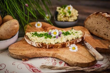 Erdäpfelkas - Auf einem schmetterlingsförmigen Holzuntersetzer ist ein Brot mit Erdäpfelkas zu sehen. Dieser ist mit Schnittlauch, Gänseblümchen und violetten Blüten geschmückt. Rechts unterhalb des Brotes liegt ein Messer. Der Holzuntersetzer befindet sich auf einem weißen Tischtuch mit rotem Blumenmuster. Links ist eine Schale mit Erdäpfeln platziert. Hinter dem Holzschneidbrett ist eine dunkelgraue, kleine Schale mit Erdäpfelkas. Rechts befindet sich ein halber Wecken Brot. Links hinter den Kartoffeln befindet sich Schnittlauch. (Foto: VrK/Franz Gleiß - Nicht zur freien Verwendung)