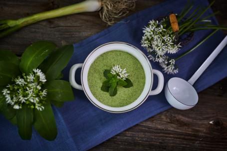 Bärlauch-Spinat-Cremesuppe - In einem weißen Topf ist die grüne Bärlauch-Spinat-Crem-Suppe angerichtet. Diese ist mit Minze und Bärlauch-Blüten verziert. Der Topf steht auf einem blauen Tischtuch, rechts neben dem Topf liegt ein weißer Schöpflöffel. Die rechte Seite des Bildes ist mit weißen Bärlauch-Blüten bestückt, die linke Seite ist mit Blüten und grünen Bärlauch-Blättern ausgestattet. Im Hintergrund des Bildes liegt noch eine grüne Pflanze. (Foto: VrK/Franz Gleiß - Nicht zur freien Verwendung)