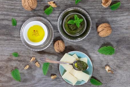 Zitronenmelissen-Pesto - 1 graues Schälchen mit grünem Pesto, garniert mit Zitronenmelisse, ein weißes Schälchen mit gelben Inhalt und der Aufschrift (Foto: VrK/Achim Mandler Photography - Nicht zur freien Verwendung)