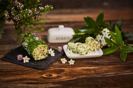 Kräuterbutter - Auf einem Holztisch wird auf einem schwarzen, kleinen Tablett die Kräuterbutter gezeigt. Das Tablett ist mit rosa und weißen Blüten verziert. Die Kräuterbutter ist von kleingeschnittenen Kräutern und Blüten umhüllt. Neben dem schwarzen Tablett befindet sich der weiße Unterteil der Butterdose. Auf dieser sind drei Butterstücke in Herzform angerichtet. Rechts daneben verschönern weiße Blüten und grüne Blätter das Bild. Im Hintergrund befinden sich der Deckel der Butterdose und ein Kräuterstrauch. (Foto: VrK/Franz Gleiß - Nicht zur freien Verwendung)