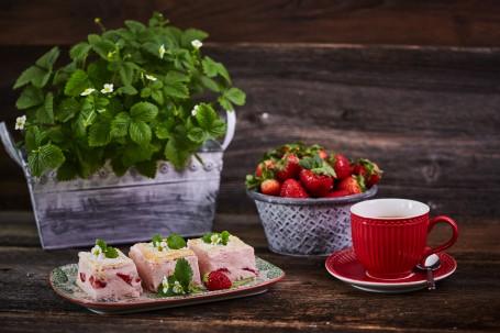 Erdbeer-Cremeschnitte - Auf einem weißen Teller mit grünem und rotem Muster werden drei Stück Erdbeer Creme Schnitte serviert. Die Stücke sind mit einer rosa Creme und roten Erdbeeren gefüllt. Jede Schnitte ist mit zwei grünen Erdbeerblättern und einer weißen Blüte dekoriert. Rechts neben dem Teller befindet sich eine rote Kaffee-Tasse mit rotem Untersetzer. Auf dem roten Untersetzer liegt ein silberner, kleiner Löffel. Dahinter ist eine graue Schüssel platziert, die mit Erdbeeren vollgefüllt ist. Links im Hintergrund ist ein grauer Blumentopf mit Erdbeerpflanzen zu sehen. (Foto: VrK/Franz Gleiß - Nicht zur freien Verwendung)