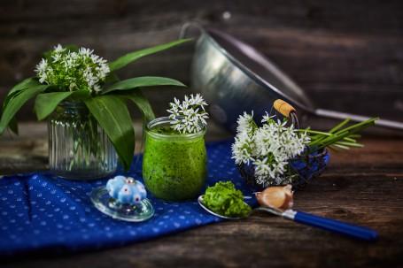 Bärlauchpesto - In der Mitte des Bildes ist ein Glas mit grünem Bärlauch Pesto zu sehen. Dieses ist mit weißen Bärlauch-Blüten verziert. Rundherum befinden sich ein Löffel mit Pesto, ein Körbchen mit Blüten und eine kleine Vase mit Bärlauch-Blättern und Blüten. Das Glas ist mit einem blauen Tischtuch unterlegt. (Foto: VrK/Franz Gleiß - Nicht zur freien Verwendung)