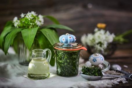 Bärlauch in Öl und Salz - Im Vordergrund befindet sich ein Glas, das mit grünem, eingelegtem Bärlauch gefüllt ist. Auf dem Deckel des Glases ist ein blau-weiß verzierter Griff. Links nebenan steht ein kleiner Krug mit Sonnenblumenöl. Der Hintergrund ist mit einer kleinen Vase mit Bärlauch-Blättern und Blüten versehen. (Foto: VrK/Franz Gleiß - Nicht zur freien Verwendung)