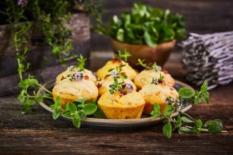 Mais-Speck-Muffins - Auf einem blau-grauen Teller befinden sich sieben Mais-Speck-Muffins. Sie sind mit rosa blühenden Kräutern und grünen Blättern dekoriert. Im Hintergrund ist ein kleines Bündel Holz, ein Blumentopf und eine Blumenkiste mit Kräutern zu sehen. (Foto: VrK/Franz Gleiß - Nicht zur freien Verwendung)