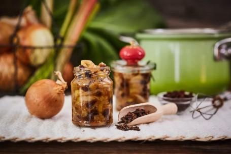 Rhabarber-Zwiebel-Chutney - Das Rhabarber-Zwiebel-Chutney befindet sich in einem Glas im Vordergrund des Bildes. Rechts nebenan ist ein hölzerner Löffel mit getrockneten Nelken. Links daneben befindet sich eine braune Zwiebel. Im Hintergrund sind ein Schneebesen, ein weiteres, gefülltes Glas, ein grüner Kochtopf und Rhabarber-Blätter zu sehen. (Foto: VrK/Franz Gleiß - Nicht zur freien Verwendung)