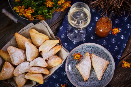 Süße Sauerrahmtascherl - Links befindet sich ein Korb mit vierzehn Stück Sauerteigtascherl. Rechts ist ein blau melierter Teller mit zwei Stück. Dieser ist mit einer orangen Blüte versehen. Dahinter stehen ein Glas mit Weißwein und ein Gefäß mit Marmelade. Den Untergrund bilden ein blaues Tischtuch und ein hölzerner Tisch. (Foto: VrK/Franz Gleiß - Nicht zur freien Verwendung)