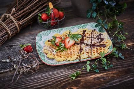 Waffeln - Die Waffeln sind auf einem weißen Teller mit grünem Muster platziert. Darauf befinden sich ebenfalls weiße Blüten, Erdbeeren und Schokosauce. Im Hintergrund sind ein Körbchen mit Erdbeeren, ein Bündel Holz und eine grüne Pflanze zu sehen. (Foto: VrK/Franz Gleiß - Nicht zur freien Verwendung)