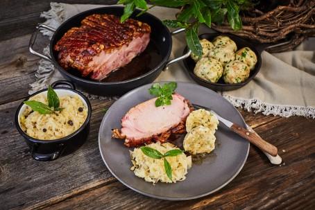 Omas Schweinsbraten - Auf einem grauen Teller ist eine Scheibe Schweinsbraten mit zwei kleinen Stücken Semmelknödel und Sauerkraut angerichtet. Links neben dem Teller befindet sich ein Kochtopf mit Sauerkraut und Pfefferkörnern. Im Hintergrund stehen zwei schwarze Pfannen, eine mit dem saftigen Braten und eine kleinere mit sechs Stück Semmelknödel. (Foto: VrK/Franz Gleiß - Nicht zur freien Verwendung)