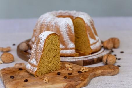 Kaffee-Nuss-Gugelhupf - Auf einem Holzbrett mit Haltegriff ist im Vordergrund ein Stück Gugelhupf zu sehen. Er hat eine gelb-bräunliche Farbe und ist mit Staubzucker bestreut. Vor den Kuchenstück liegen Nussstückchen und Kaffeebohnen zur Deko. Im Hintergrund ist der Rest des Gugelhupfes zu sehen, er steht ebenfalls auf einem Holzbrett und ist mit Staubzucker bestreut. Rund um den Kuchen sind einige Nüsse mit Schale und Kaffeebohnen aufgelegt. (Foto: VrK/Achim Mandler Photography - Nicht zur freien Verwendung)