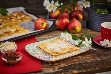 Mürber Apfelkuchen - Der Apfelkuchen ist mit Mandelblättchen und Staubzucker bestreut. Eine kleine Kuchengabel liegt bereit, weiße Blüten und grüne Blätter verzieren den Kuchen. Der Kuchen liegt auf einem weißen Teller mit buntem Muster, links daneben befinden sich zwei kleine Schalen mit Haselnüssen und Mandelblättern. Im Hintergrund ist das Backblech mit dem Kuchen zu sehen, rechts daneben steht eine Obstschüssel mit Äpfeln. (Foto: VrK/Franz Gleiß - Nicht zur freien Verwendung)