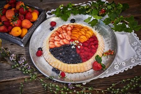 Früchtekuchen - Der Früchtekuchen wird auf einem silbernen Teller serviert. Die Oberfläche des Kuchens bilden Heidelbeeren, Himbeeren, Erdbeeren und Marillen. Zusätzlich ist der Teller mit Ribiseln geschmückt. Links im Hintergrund befindet sich eine Obstschale mit Früchten. Der Teller ist mit einem weißen Tischtuch mit Spitzen unterlegt. (Foto: VrK/Franz Gleiß - Nicht zur freien Verwendung)