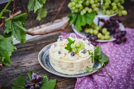 Weincremetorte - Die Weitcremetorte steht auf einem blau-melierten Teller. Dieser befindet sich auf einem  dunkelbraunen Holztisch. Der Teller ist mit einem violetten Tischtuch mit weißen Verzierungen unterlegt. Auf der Weincremetorte sind 8 Kügelchen aus Schlagobers, die mit violetten Blüten bedeckt sind. In der Mitte befinden sich grüne Weintrauben mit einem grünen Blatt. Im Vordergrund des Bildes sind dunkelblaue Weintrauben, die auf grünen Blättern liegen. Im Hintergrund befinden sich Weinpflanzen mit einem Holzspalier. (Foto: VrK/Franz Gleiß - Nicht zur freien Verwendung)