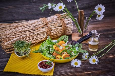 Gebackene Polentascheiben - Auf einem gelben Tischtuch sind auf einem Teller gebackene Polentascheiben angerichtet. Sie sind mit grünem Salat und Gänseblümchen geschmückt. Rechts nebenan steht ein kleiner Krug. Margeriten verzieren das Bild. (Foto: VrK/Franz Gleiß - Nicht zur freien Verwendung)