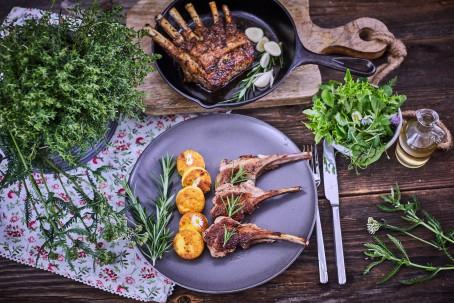 Lammkotelett - Auf einem schwarzen Teller liegen drei Stück Lammkotelett. Als Beilage sind fünf Stück Polentascheiben beigefügt. Der Teller ist mit Rosmarin bestückt. Rechts nebenan liegen Messer und Gabel. Dahinter befindet sich eine Pfanne mit Kotelett und Knoblauch. Eine kleine Schale mit Salat ist bereitgestellt. (Foto: VrK/Franz Gleiß - Nicht zur freien Verwendung)