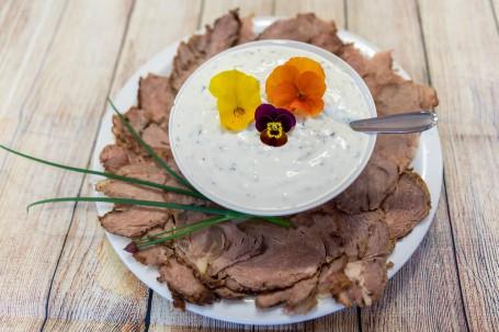 Roastbeef mit Kräutertatar - Auf einem hellen Holzhintergrund steht ein weißer runder Teller. AUf dem Teller liegen fein aufgeschnittene Roastbeefscheiben. In der Mitte steht eine weiße Schüssel mit der weißen Kräutertatar, die Kräuter sind zu erkennen. Auf der Kräutertatar liegen dekorativ 3 Blüten eine gelbe, eine orange und eine lila farbige. In der Kräutersoße steckt ein silberner Löffel. (Foto: VrK/Achim Mandler Photography - Nicht zur freien Verwendung)