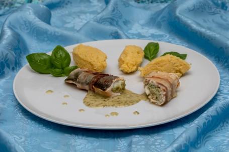 Forellenröllchen im Speckmantel - Auf einem hellbaluen Tischtuch steht ein runder weißer Teller. Auf dem Teller liegen im Vordergrund 2 mit Speck umwickelte zu Röllchen geformte Fischfilets. In der Mitte der Röllchen befindet sich eine grünliche Fülle. Die Basilikum-Weißweinsauce ist unter den Röllchen am Teller aufgetragen. Im hinteren Teil des Tellers leigen 3 Polentanockerl und einige Basilikumblätter zur Deko. (Foto: VrK/Achim Mandler Photography - Nicht zur freien Verwendung)