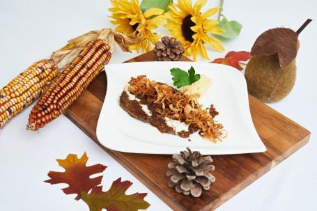 Zwiebelrostbraten - Auf einem braunen Holzbrett steht ein weißer Teller. Auf dem Teller befindet sich ein Stück des Zwiebelrostbraten. Über dem Stück sind angebratene Zwiebelringe gestreut. Im hinteren Bereich des Tellers ist eine Esslöffelgroße Portion Erdäpfelpürre zu sehen. Im Pürree steckt ein Blatt Petersilie. Rund um das Teller befindet sich herbstliche Dekoration (Zapfen, Maiskolben, Blätter, Sonnenblumen). (Foto: Foto Herbst - Nicht zur freien Verwendung)