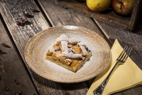 Apfelschlankel - Auf einem Holztisch steht ein brauner runder Teller. Auf dem Teller befindet sich ein quadratisches Stück Apfelschlankel, das mit Staubzucker bestreut ist. Rechts neben dem Teller leigt eine gelbe Serviette, die zu einem Dreieck gefalten ist, darauf liegt eine silberne Dessertgabel. (Foto: VrK/Alexander Stiegler - Nicht zur freien Verwendung)