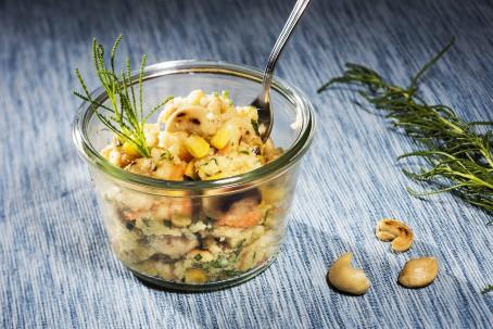 Bunter Hirsesalat mit Maroni - In einem kleinen Dessertglas ist der bunte Hirsesalat angerichtet. Einzelne Cashewnüsse sind zu erkennen. Eine gabel steckt im Salat. Neben dem Glas liegen 3 Cashewnüsse als Deko. (Foto: VrK/Alexander Stiegler - Nicht zur freien Verwendung)